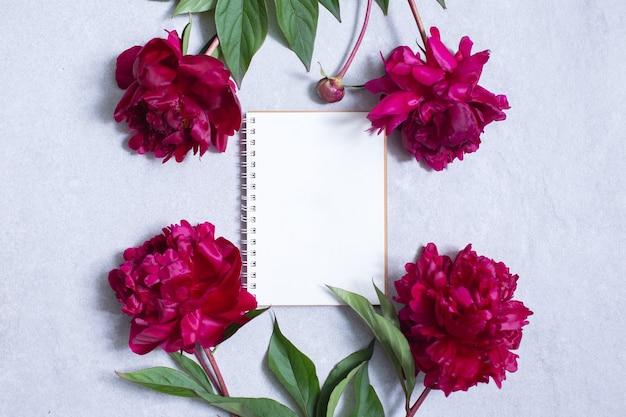 Kwiaty piwonii i pusty notatnik do planowania lub życzeń
