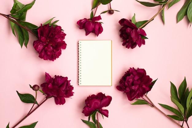Kwiaty piwonii i pusty zeszyt do planowania lub życzeń na różowo.