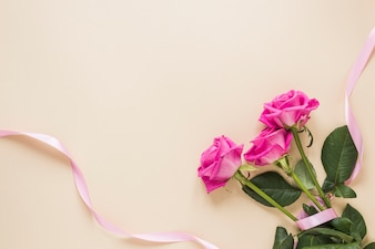 Kwiaty róży z wstążką na stole
