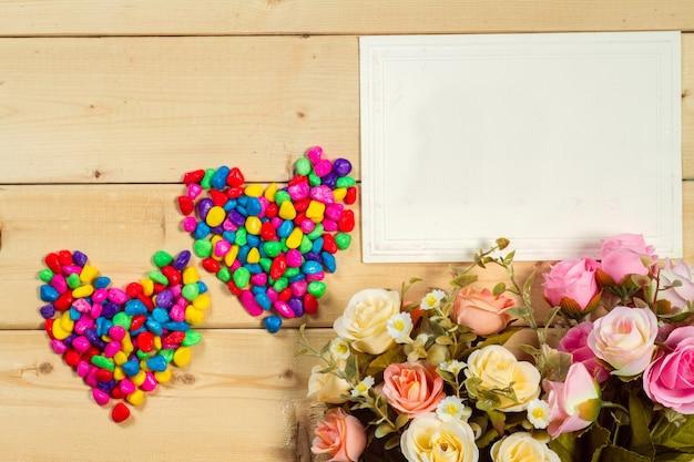 Kwiaty róż i pusty znacznik tekstu na drewnianym tle pastelowy odcień