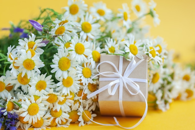 Kwiaty rumianku i pudełko prezentowe lub prezentowe na żółto