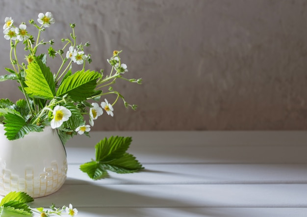 Kwiaty truskawki w wazie na starym tle
