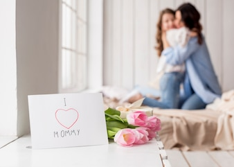 Kwiaty tulipanów i kartkę z życzeniami na stole