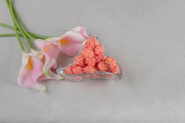 Kwiaty ułożone obok półmiska z popcornowymi cukierkami na marmurowym stole.