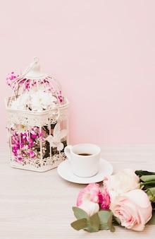 Kwiaty w białej klatce; filiżanka kawy i róże na drewniane biurko na różowym tle