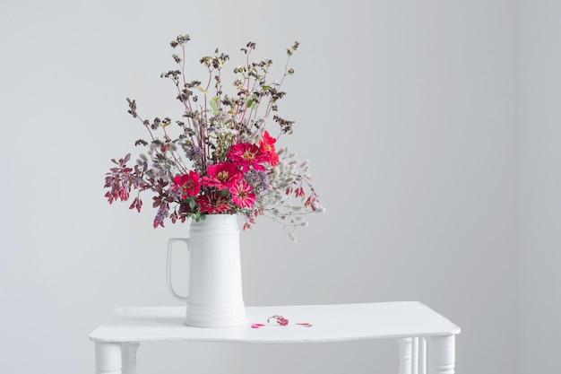 Kwiaty w białym dzbanku na białym tle