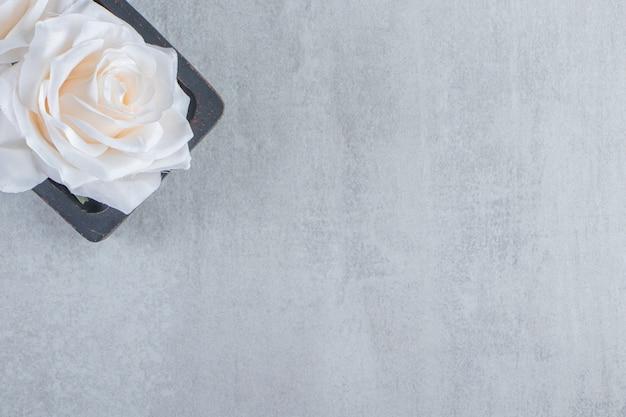 Kwiaty w drewnianym talerzu, na białym stole.