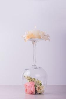 Kwiaty w kieliszku do wina i świecy.
