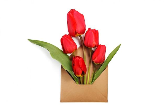 Kwiaty w kopercie. czerwone tulipany w kopercie rzemieślniczej. koncepcja wiosny