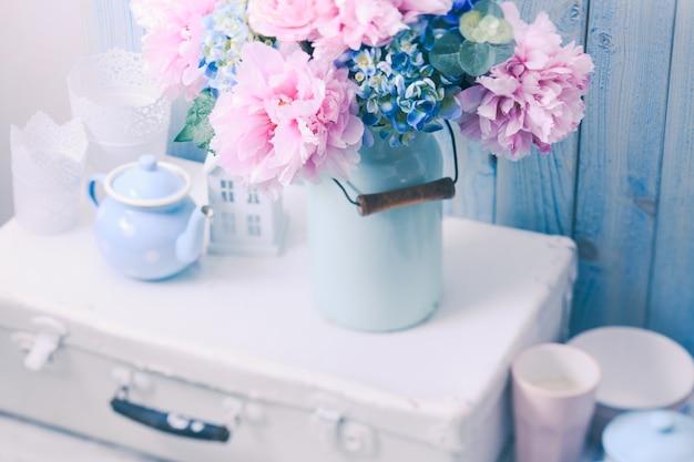 Kwiaty w niebieskiej puszce vintage na białej torbie retro i naczyniach kuchennych
