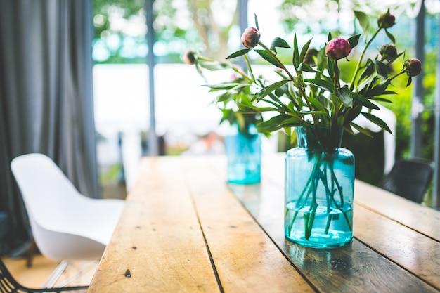 Kwiaty w niebieskim wazonie na stole