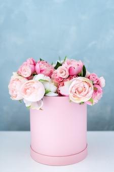 Kwiaty w okrągłym luksusowym pudełku prezentowym. bukiet różowych i białych piwonii w kartonowym pudełku. makieta kapelusz pole kwiatów z bezpłatnym copyspace dla tekstu. dekoracja wnętrz w pastelowych kolorach.