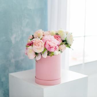 Kwiaty w okrągłym luksusowym pudełku prezentowym. bukiet różowych i białych piwonii w kartonowym pudełku. makieta kapeluszowego pudełka z kwiatami. dekoracja wnętrz w pastelowych kolorach.