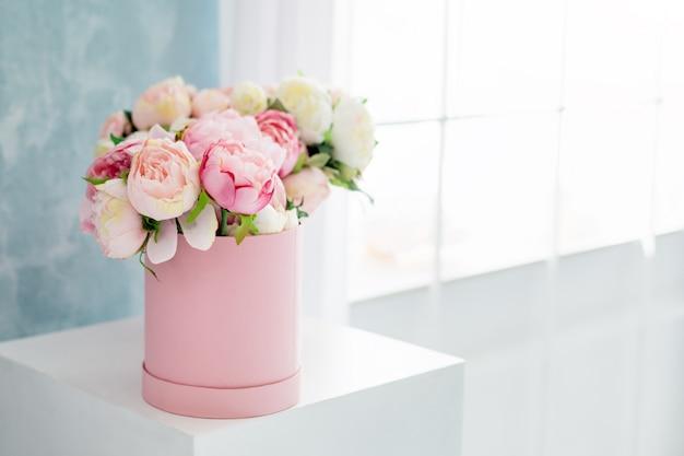 Kwiaty w okrągłym luksusowym pudełku prezentowym. bukiet różowych i białych piwonii w papierowym pudełku w pobliżu okna. makieta kapeluszowe pudełko kwiatów z bezpłatnym miejscem na tekst. dekoracja wnętrz w pastelowych kolorach.