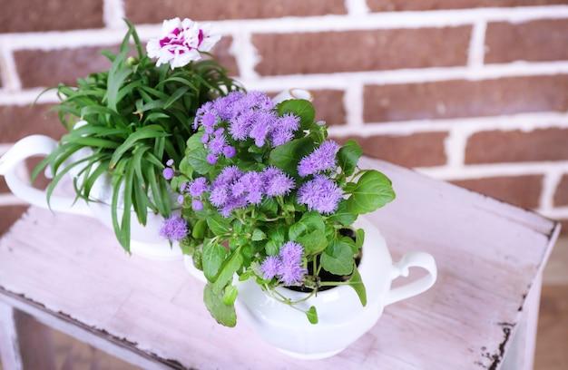 Kwiaty w ozdobnych doniczkach na drewnianej drabince, na cegłach