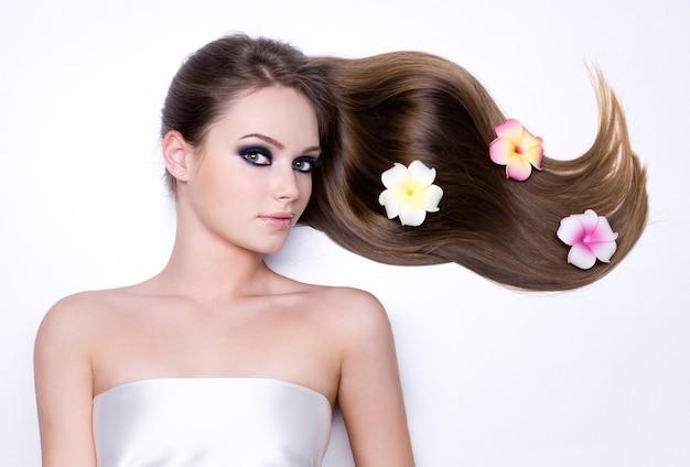 Kwiaty w pięknych, długich, prostych, błyszczących włosach dziewczyny na białym tle