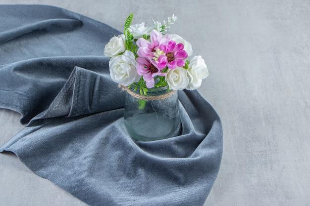 Kwiaty w słoiku na kawałku materiału, na białym tle. zdjęcie wysokiej jakości