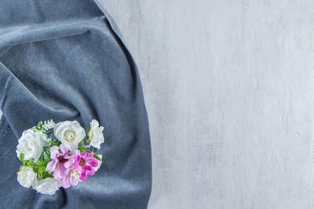 Kwiaty w słoiku na kawałku materiału, na białym tle.