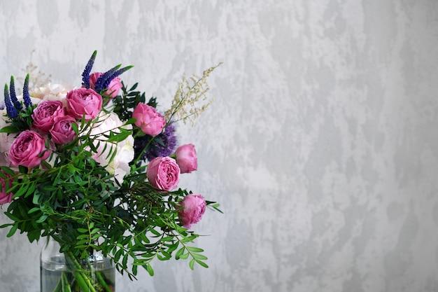 Kwiaty w szklanym słoju na szarym tle betonu. vintage wystrój domu. skopiuj miejsce na tekst.