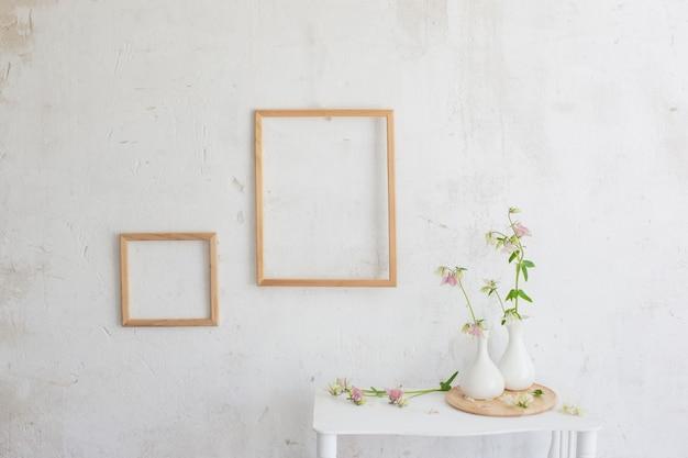 Kwiaty w wazonie i drewniane ramki na białym wnętrzu