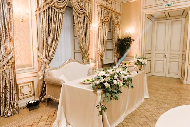 Kwiaty w złotym wazonie na luksusowym świątecznym stole