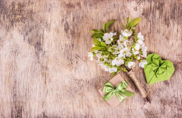 Kwiaty wiśni, papierowe serce i pudełko na drewniane tła