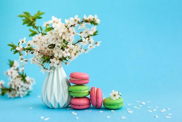 Kwiaty wiśni w niebieskim wazonie i różowym pudełku oraz francuskie kolorowe makaroniki na niebiesko