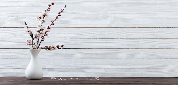 Kwiaty wiśni w wazonie na powierzchni drewnianych