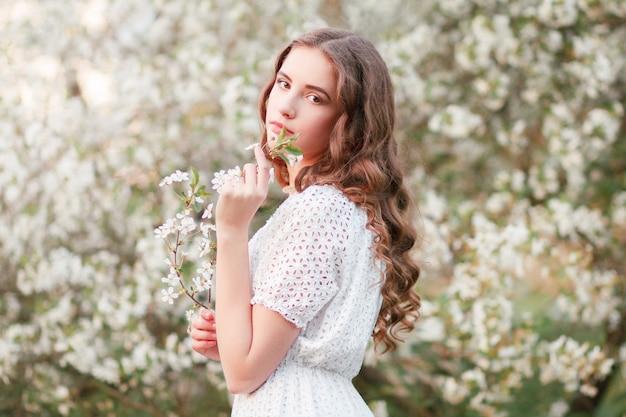 Kwiaty wiśni. wiosna. młoda czuła dziewczyna jest wśród kwitnących drzew. czułość