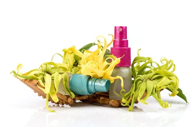 Kwiaty ylang-ylang lub cananga odorata i wyekstrahowane w butelkach z rozpylaczem na białym tle.