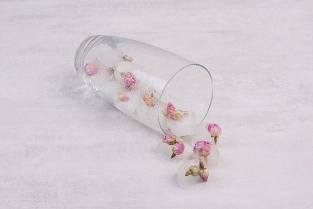Kwiaty zamrożone w kostkach lodu na białej powierzchni.