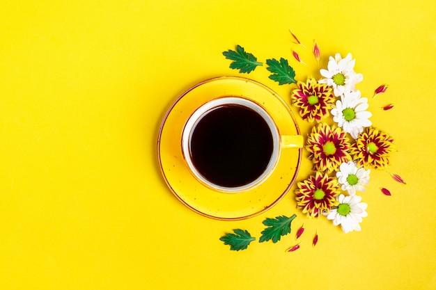 Kwiaty, zielone liście i kubek gorącej kawy