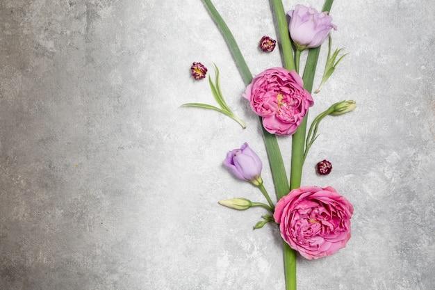 Kwiecista ramka na szarym tle. widok z góry i miejsce na kopię. delikatne liliowe róże i eustoma. kompozycja narożna. wysokiej jakości zdjęcie