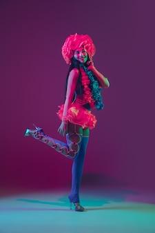 Kwitnąć. hawajska modelka brunetka na fioletowej ścianie w neonowym świetle. piękne kobiety w tradycyjnych strojach, uśmiechnięte, tańczące i bawiące się. jasne święta, kolory uroczystości, festiwal.