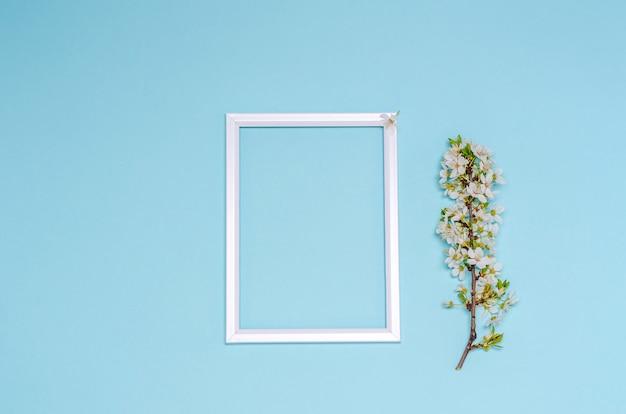 Kwitnąca gałąź wiśni z białymi kwiatami i ramką z miejscem na tekst na niebieskim tle. koncepcja sezonowości, wiosna. leżał płasko, kopia przestrzeń. widok z góry.