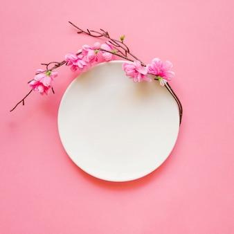 Kwitnąca gałązka blisko talerza