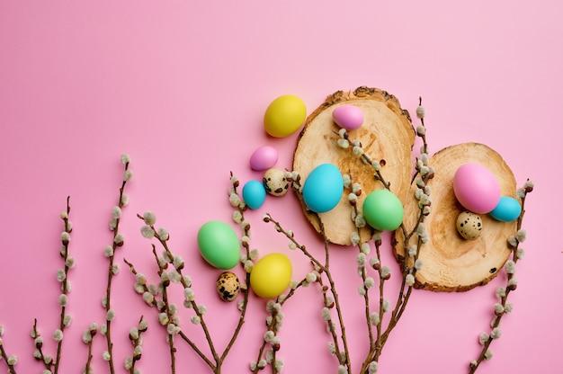 Kwitnąca gałązka wierzby i pisanki na drewnianych podstawkach, różowy stół. wiosenne kwiaty i paschalne jedzenie, świeża dekoracja kwiatowa na święta, symbol wydarzenia