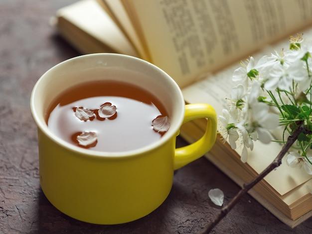 Kwitnąca wiosną gałąź wiśni, filiżanka herbaty i książka