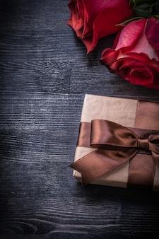 Kwitnące czerwone róże zawijali giftbox na drewnianym tło wakacji pojęciu