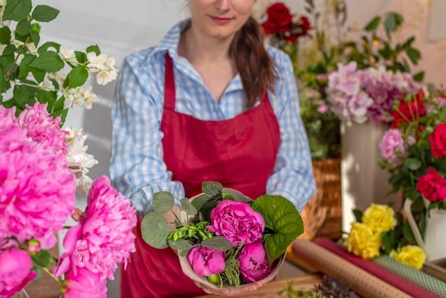 Kwitnące piwonie, sprzedawca kwiatów. biznes florystyczny. układ bukietów.