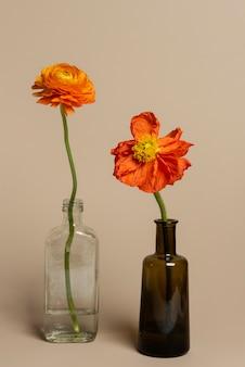 Kwitnące pomarańczowe kwiaty jaskier w wazonie butelkowym