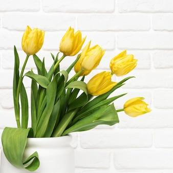 Kwitnące żółte kwiaty w białym wazonie na tle dekoracyjnego ceglanego muru z kopią. wiosenne kwiaty na dzień kobiety lub matki.