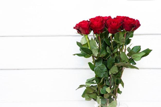 Kwitnący bukiet czerwonych róż w wazonie z przezroczystego szkła