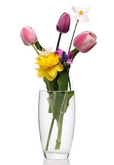 Kwitnący bukiet różnych kwiatów w przezroczystym wazonie z wodą