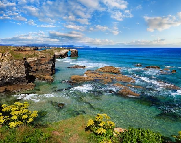 Kwitnący letni krajobraz wybrzeża kantabrii z błękitnym malowniczym niebem (cathedrals beach, lugo, galicja, hiszpania).
