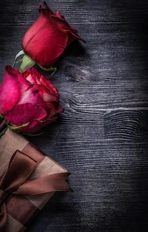Kwitnący perfumowi rosebuds pakowali giftbox na drewnianym tło wakacji pojęciu