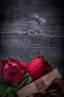 Kwitnący rosebuds pakowali prezenta pudełko na drewnianym tło wakacji pojęciu
