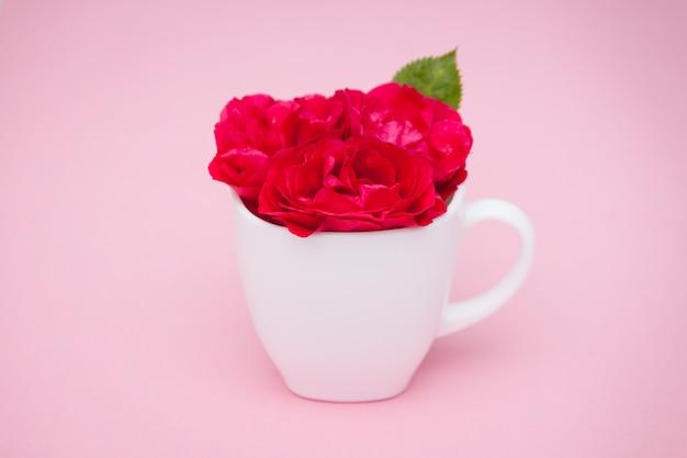 Kwitnie czerwone róże w filiżance na różowym tle. leżał z płaskim, widok z góry, tle kwiatów.