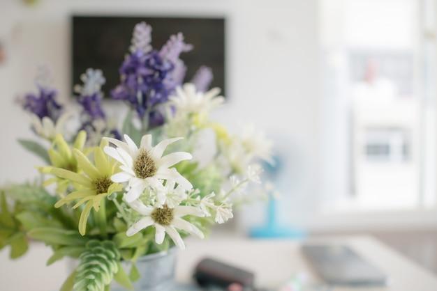 Kwitnienie fałszywego kwiatu i zieleni liść na stole.