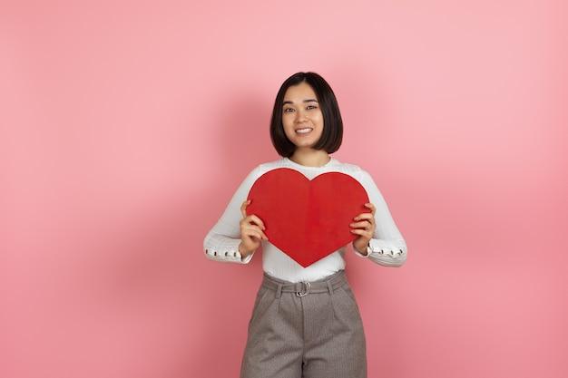 L młoda azjatykcia kobieta trzyma wielkie czerwone papierowe serce